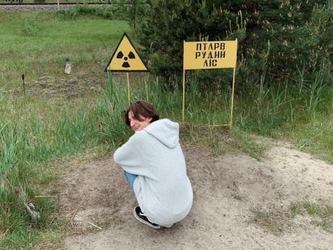 Un visitante se inclina cerca de un símbolo de advertencia de radiación en la zona de exclusión.