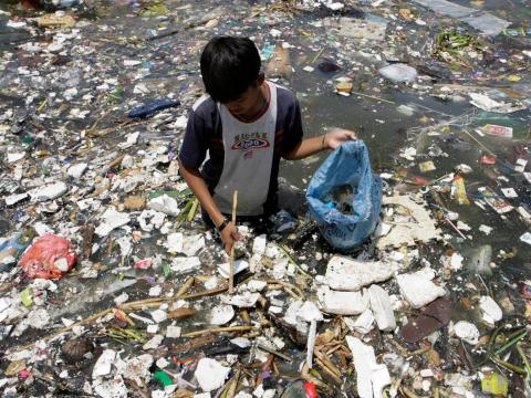 Un niño en Filipinas recoge plástico cerca de la costa