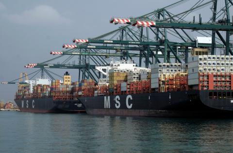 Unos buques descargan mercancías en el puerto de Valencia.