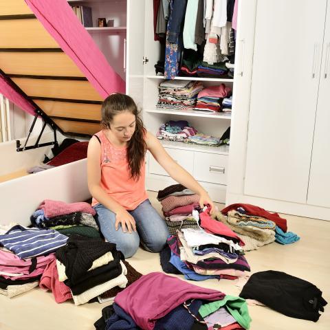 Chica organizando la ropa en el suelo