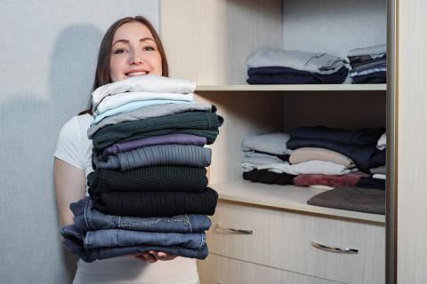 Chica sujetando una pila de ropa