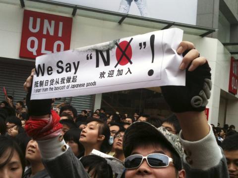 """En China, un manifestante con una pancarta de """"boicot a los productos japoneses"""" fuera de una tienda de Uniqlo de Japón durante las protestas por las islas Diaoyu y Senkaku contra Japón en 2010."""