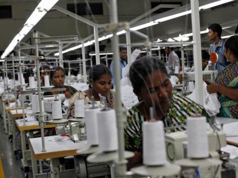 Empleados cosen ropa en una fábrica de ropa en la India.