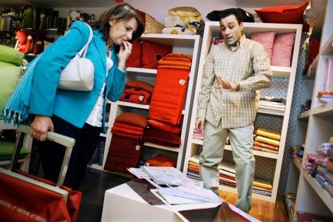 Un comerciante textil atiende a una clienta en su tienda