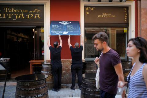 Dos camareros colocan la tabla de precios de un bar en su terraza
