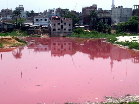 El agua de una zanja se vuelve roja a medida que se vierten sustancias químicas y deshechos de una fábrica.