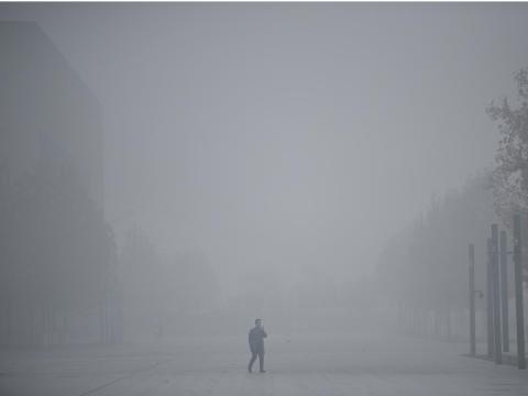 Un hombre utiliza su móvil mientras camina entre el 'smog' en Tianjin, China.