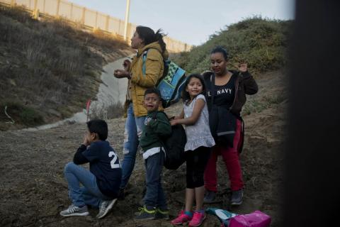 Honduran migrants surrender to the US Border Patrol after crossing the border wall into the US.