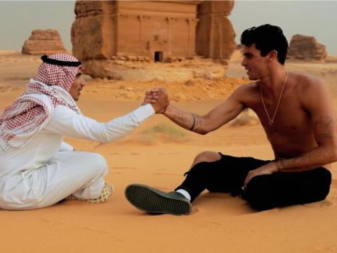 La megaestrella de Instagram Jay Alvarez le da la mano a un hombre saudí que lleva un keffiyeh y thawb en el centro de patrimonio de Arabia Saudí Mada'in Saleh.