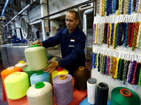 Un empleado trabaja en una fábrica de hilos