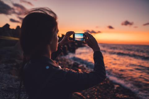 Una mujer haciendo una foto al horizonte con un teléfono