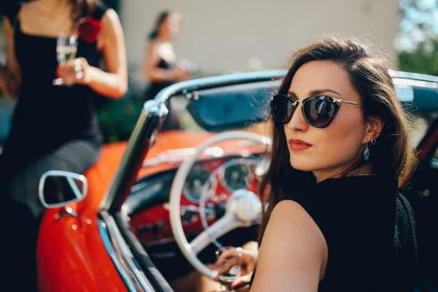 Una mujer millonaria conduce un coche de lujo.