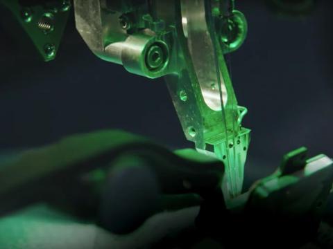 El robot parecido a una máquina de coser de Neuralink perforaría los alambres en el cerebro del sujeto.