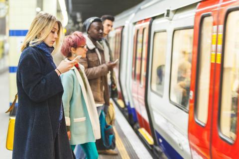 Pasajeros con el móvil esperan el metro