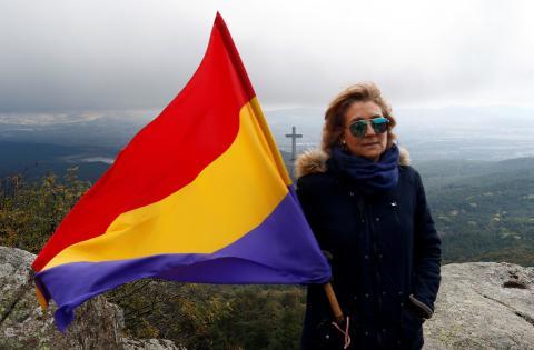 Una persona sujeta una bandera republicana junto al Valle de los Caídos el día que exhuman a Franco.