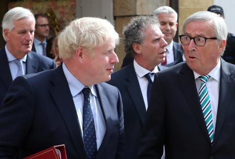 El primer ministro británico, Boris Johnson, y el presidente de la CE, Jean-Claude Juncker, con el negociador de la UE para el Brexit, Michel Barnier, al fondo de la imagen