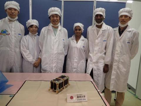 Los equipos de desarrollo de CubeSat y los funcionarios de JAXA posan con una demostración a pequeña escala del ascensor orbital STARS-Me, en agosto de 2018.