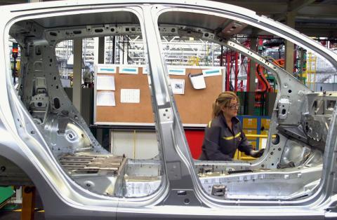 Una trabajadora en una cadena de montaje de una compañía automovilística