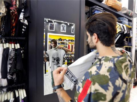 Un hombre iraquí se mira en el espejo mientras compra.