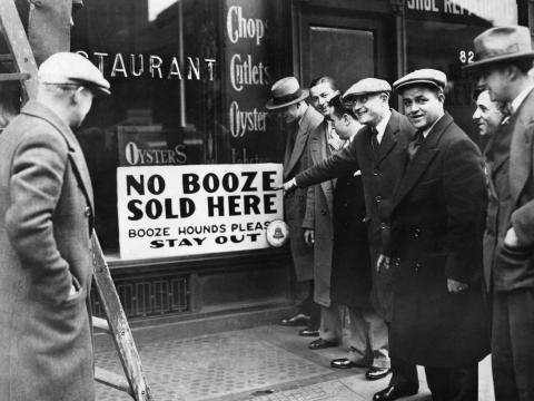 """People by a Prohibition sign reading, """"No booze sold here."""""""