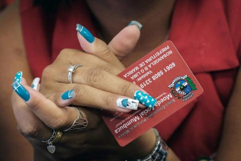 "A cashier holds a ""mumbuca"" card at a pharmacy in Marica, Brazil."