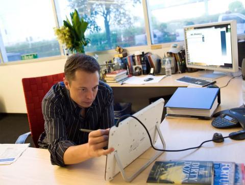 Elon Musk, CEO de Tesla, mira la pantalla de un tablet