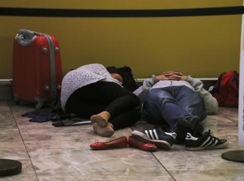Pasajeros durmiendo en el aeropuerto de Alicante.