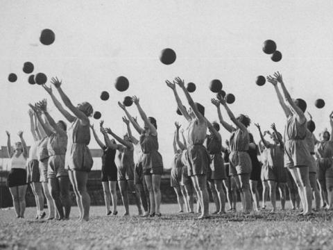 Gente lanzando pelotas sincronizadas en una clase de gimnasia de los años veinte.