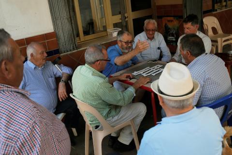 Un grupo de jubilados juega una partida de dominó en una terraza en Fuengirola