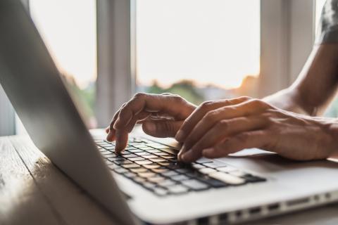 Un hombre escribiendo en un ordenador.