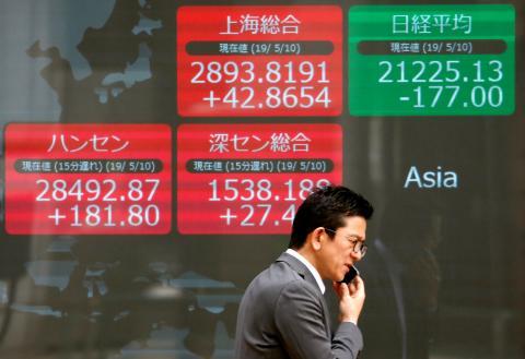 Un hombre pasa delante de la cotización de los mercados asiáticos.