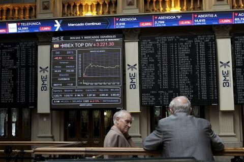 Dos inversores conversan ante las pantallas de la Bolsa de Madrid