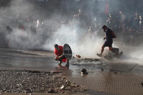 Manifestantes se cubren de la policía en Chile.
