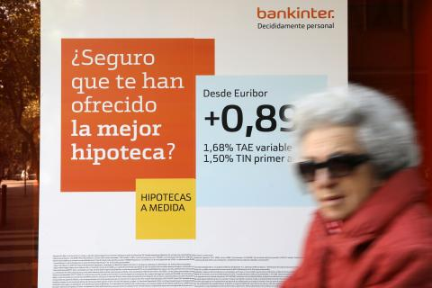 Una mujer pasa ante un anuncio de hipotecas en una sucursal bancaria
