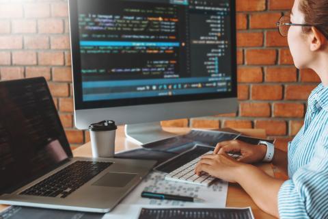 Mujer programando en diferentes ordenadores.