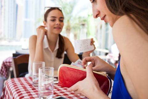 Mujeres pagando en un restaurante.