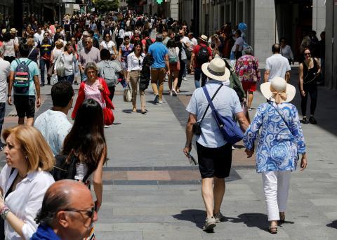 Una pareja de turistas pasea entre la gente en la calle Preciados de Madrid