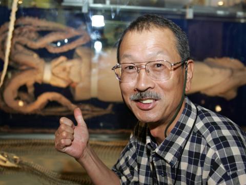 El investigador japonés Tsunemi Kubodera sonríe mientras muestra un calamar gigante en exhibición en el Museo Nacional de Ciencias en Tokio el 28 de septiembre de 2005.