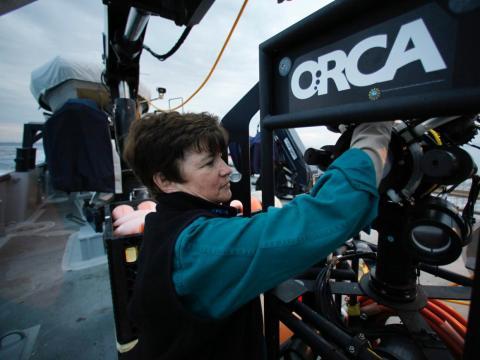 """La científica marina Edith Widder inspecciona una cámara de video Eye-in-the-Sea"""" a bordo del buque de investigación Vessel Point Lobos."""
