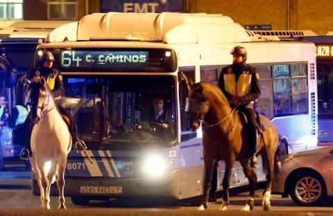 Agentes de policía a caballo escoltan a un autobús de la EMT durante la huelga general de 2012