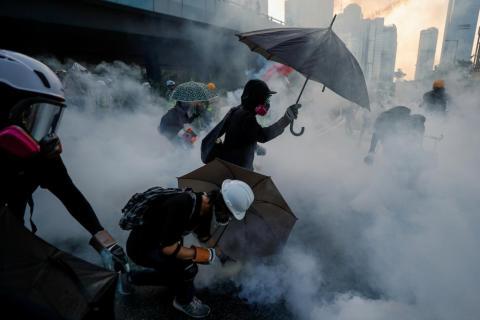 Los manifestantes se protegen con paraguas entre gases lacrimógenos durante una manifestación cerca del Complejo del Gobierno Central en Hong Kong el 15 de septiembre.