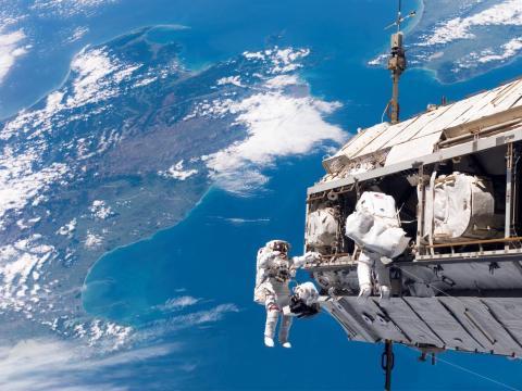 Con Nueva Zelanda y el Estrecho de Cook en el Océano Pacífico de fondo, los astronautas Robert L. Curbeam Jr. (a la izquierda) y Christer Fuglesang (a la derecha) participan en una misión extravehicular (EVA). 12 de diciembre de 2006.