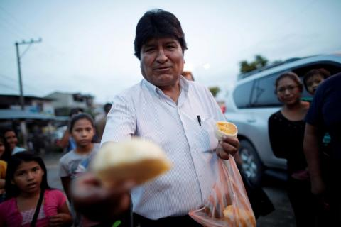 El ex presidente de Bolivia y ex candidato presidencial del Movimiento al Socialismo (MAS), Evo Morales, ofrece frutas a los pobres en una calle de Shinahota, Bolivia, el 19 de octubre.