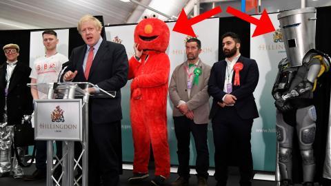 Boris Johnson da un discurso tras ganar su escaño junto a dos competidores disfrazados