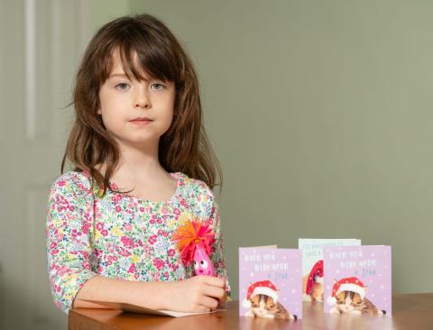 Florence Widdicombe, de 6 años, escribe en una tarjeta de Navidad de Tesco del mismo paquete en el que encontró un mensaje de un presunto prisionero chino.