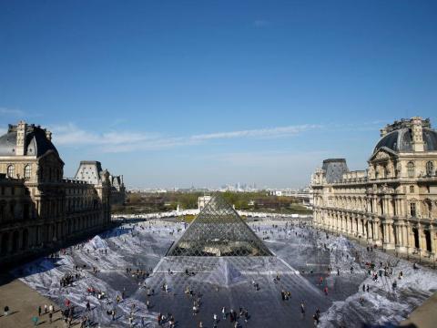 Los turistas caminan sobre una obra fotográfica gigante de JR en el patio principal del Museo del Louvre.