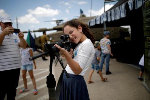Una niña juega con un rifle después de la ceremonia del Día del Recuerdo de los soldados caídos en el sitio conmemorativo del ejército de Latrun en Israel el 8 de mayo.