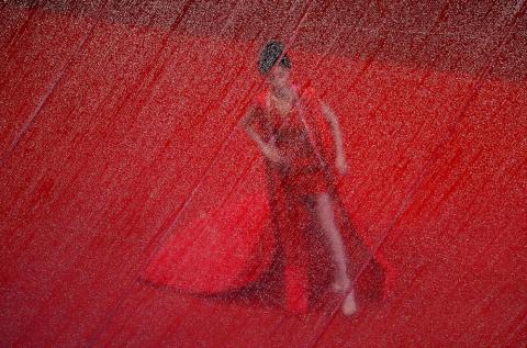 """Una invitada en la alfombra roja a través de una lona cubierta de lluvia durante la presentación de la película """"Frankie"""" en el 72º Festival de Cine de Cannes, en Cannes, Francia, el 20 de mayo."""