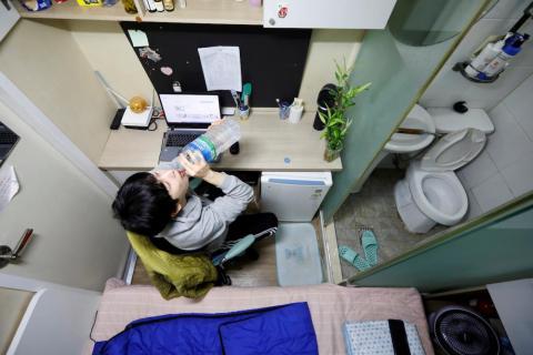 Kim Jae-hoon se sienta en un reducido cubículo llamado goshi-won, donde vive, en Suwon, Corea del Sur, en noviembre.