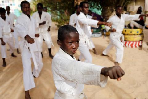 Un estudiante del Corán llamado Demba, de 8 años, asiste a un entrenamiento de karate en el patio de la Maison de la Gare, una organización que ayuda a los niños de la calle talibe a reintegrarse en la sociedad, en Saint-Louis, Senegal.